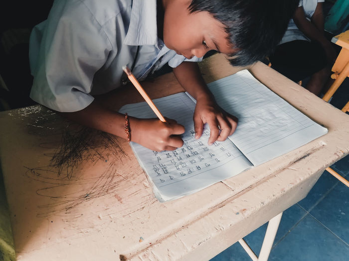 High angle view of boy writing on book in classroom