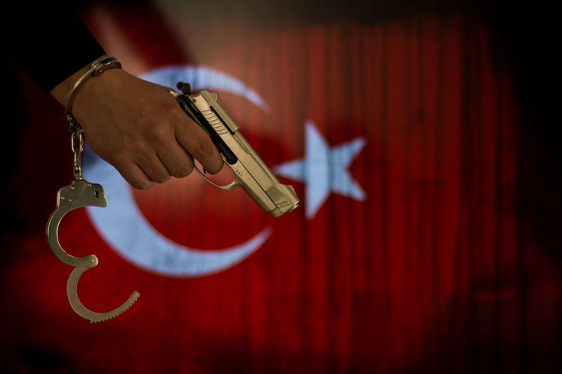 Cropped hand of male criminal holding gun against turkish flag