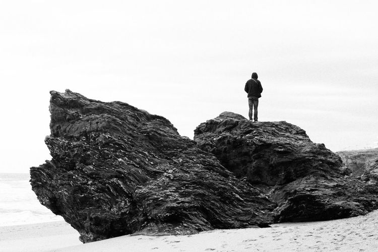 Rear view of man standing on rock at beach against sky