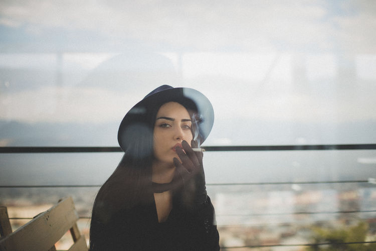 Portrait of beautiful young woman seen through glass window smoking while sitting against railing