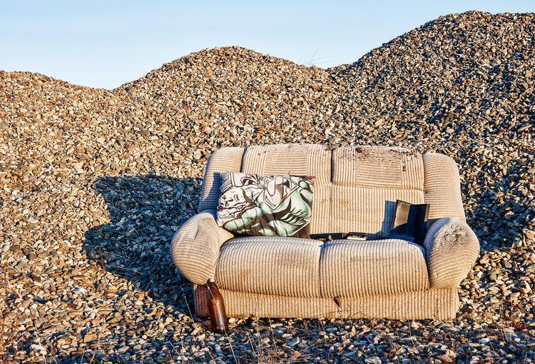 Chairs on rocks on beach against sky