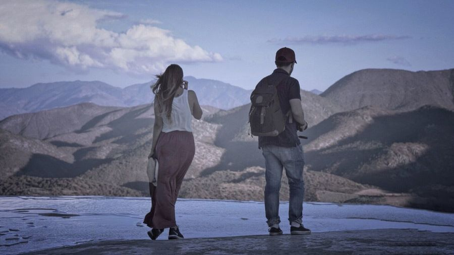 Friends standing on desert against mountains