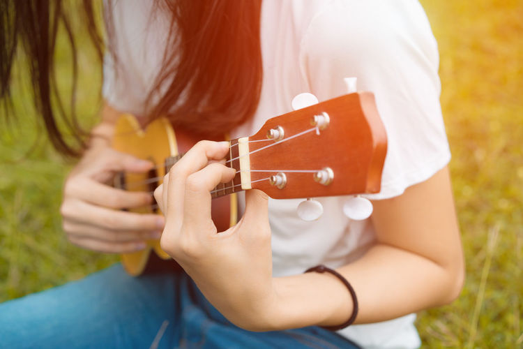 Midsection of woman playing ukulele on grass