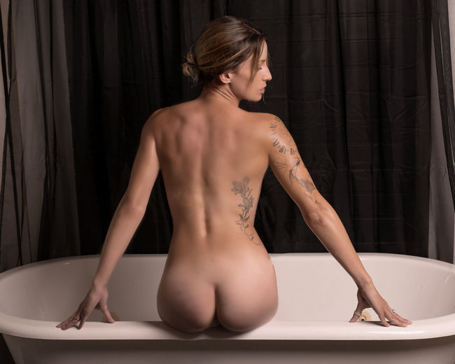 Rear view of naked young woman sitting on bathtub at home