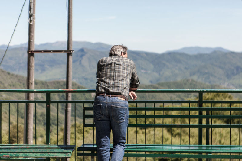 Rear View Of Man Standing In Front Of Mountains
