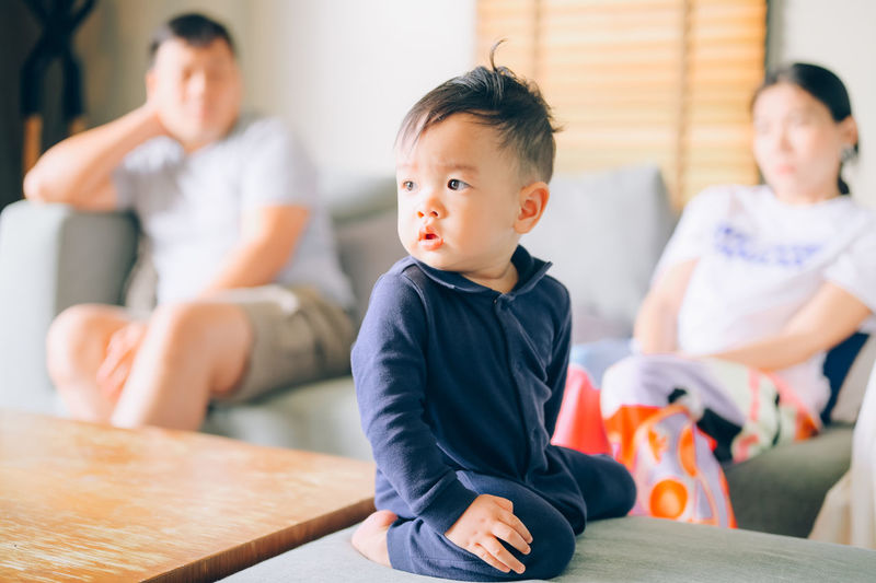 Cute boy looking away while sitting at home