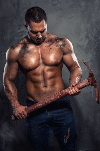 Shirtless Muscular Worker Holding Pick Axe While Standing Against Wall