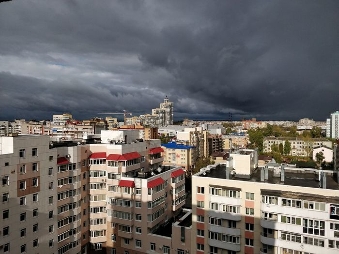 Buildings in city against dramatic sky