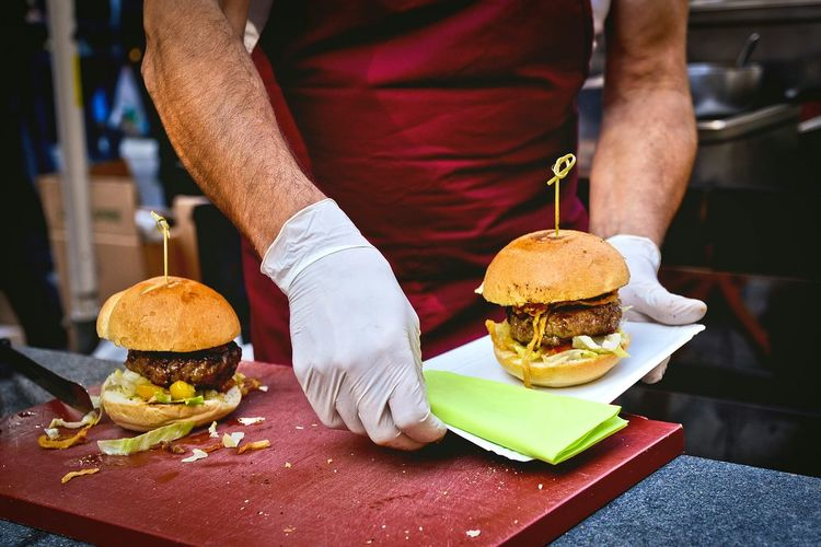 Midsection Of Man Preparing Burger At Table In Kitchen