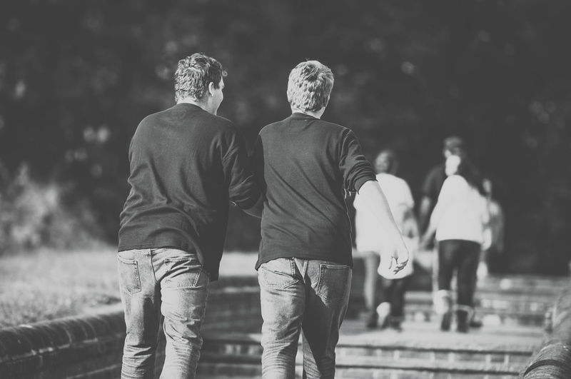 Two Brothers Walking Together Young Adult Boy Boys Casual Clothing Friendship Leisure Activity Men Nature Outdoors Park People Real People Rear View Side By Side Togetherness Two People Walking