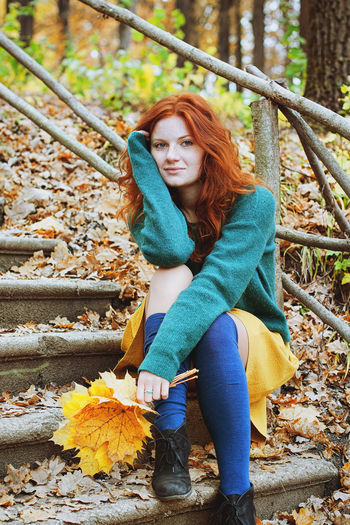 Portrait of young redhead woman sitting on autumn leaves