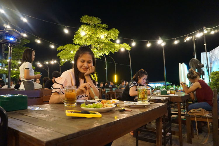 Togetherness Smiling People Bonding Daughter Leisure Activity Group Of People Women Real People Sitting Lifestyles Food And Drink Table Food Night Casual Clothing Men Females Illuminated Eating Adult