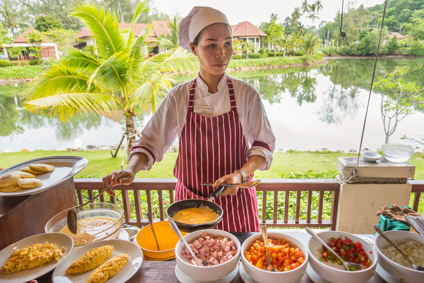Trat, Thailand - May, 21, 2017 : Unidentified name woman chef was making scrambled eggs for breakfast at the restaurant of Klong Prao Resort in Koh Chang island Trat, Thailand. Day Editorial  Food Food And Drink Freshness Front View Healthy Eating Illustrative Illustrative Editorial One Person Outdoors People Real People Standing Thailand Variation Vegetable Young Adult