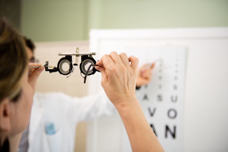 Midsection of doctor showing alphabets to patient during eye test