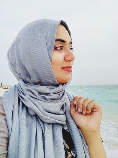 Smiling Young Woman Wearing Hijab Looking At Sea