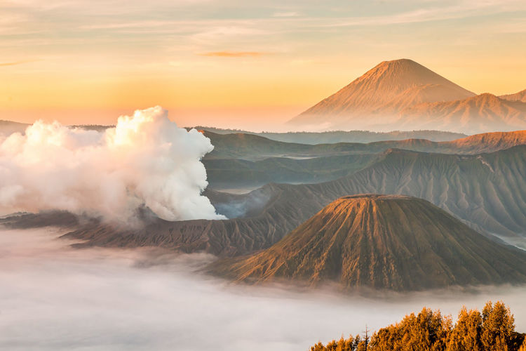 Smoke emitting from volcanic landscape against sky during sunset