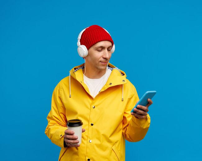 Full length of man using mobile phone against blue sky