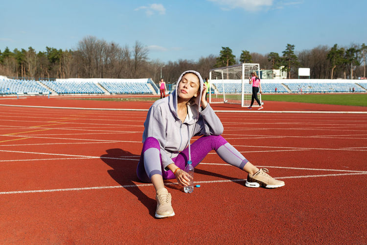 Full length of woman wearing hoodie sitting on running track