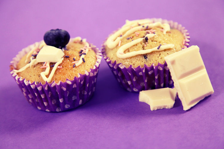 Close-up of cup cakes over purple background