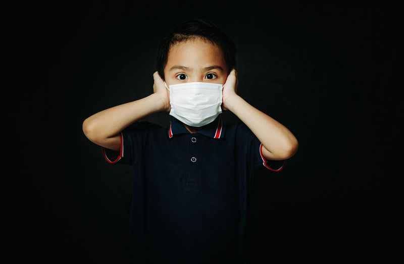 Portrait of boy standing against black background