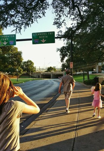 exploring the city People Kids Outside Streetphotography Walking Taking Pictures Sunlight Sidewalk Street Road Street Sign From Behind Walkway Exploring City Illuminated Sunny Illumination Tree Road Sign City Road Street Sky #urbanana: The Urban Playground