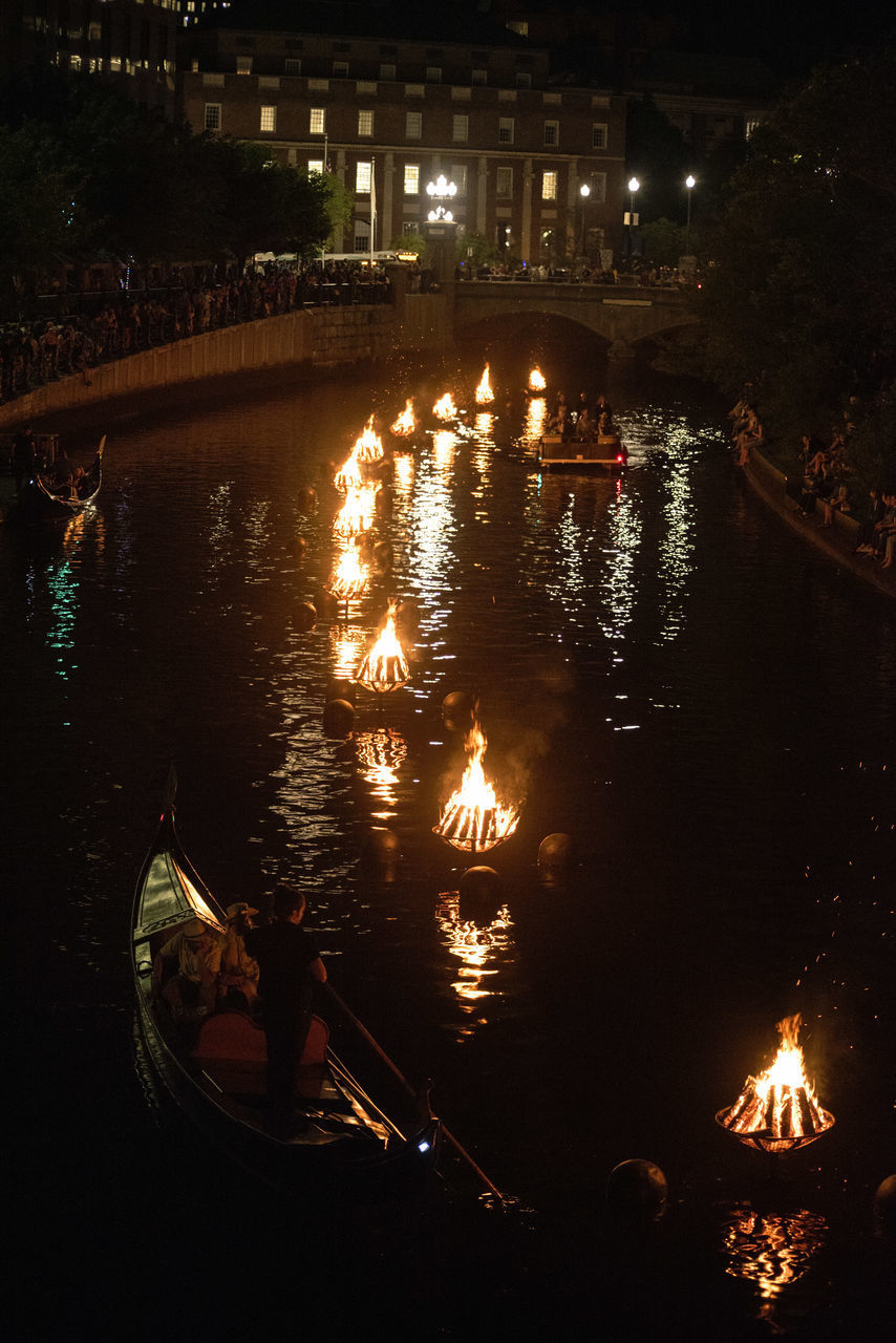 water, illuminated, night, nature, real people, reflection, burning, heat - temperature, glowing, fire, high angle view, nautical vessel, river, flame, transportation, group of people, fire - natural phenomenon, people
