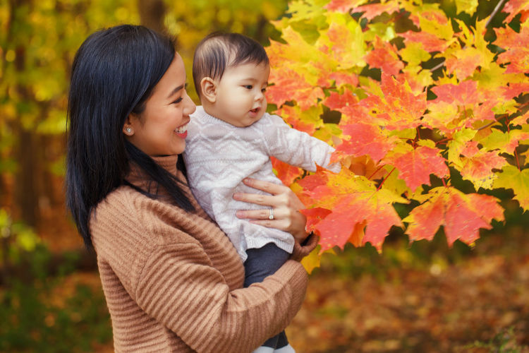Mother and daughter in park touching autumn leaf at park