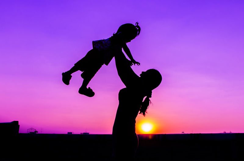 Silhouette mother holding aloft daughter against sky during sunset
