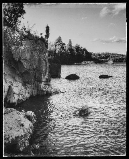 Rocks in water against sky