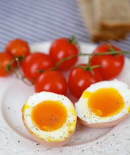 Close-up of boiled eggs with fresh cherry tomatoes in plate