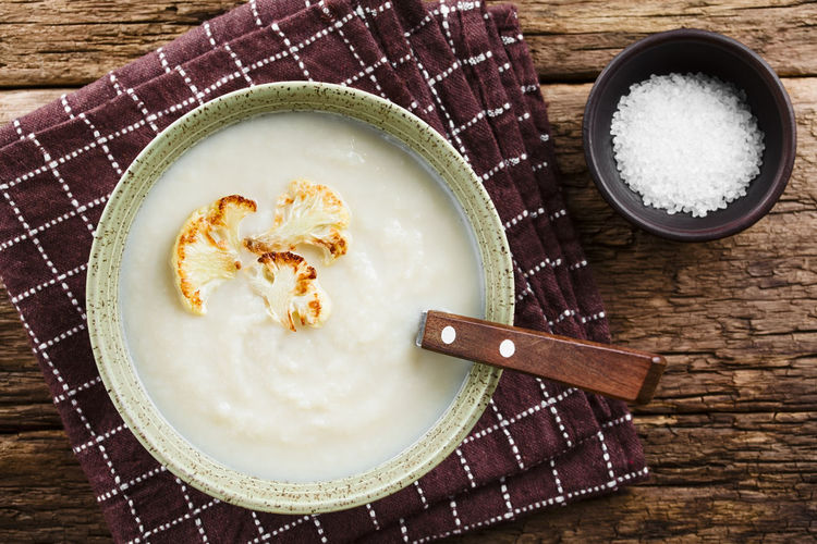 Fresh homemade cream of cauliflower soup garnished with roasted cauliflower floret slices, served in bowl with spoon, salt on the side, photographed overhead on rustic wood (Selective Focus, Focus on the soup) Food Food And Drink Freshness Bowl Healthy Eating Ingredient Ready-to-eat Fresh Natural Soup Cream Creamy Cream Soup Cauliflower Cole Cruciferous Vegetable Vegetarian Vegetarian Food Blended Puree Appetizer Healthy Meal Dish