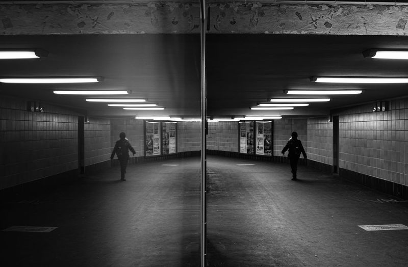 Reflection of person walking in subway station on glass