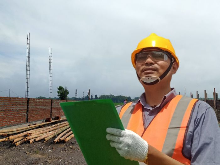 Man working at construction site against sky