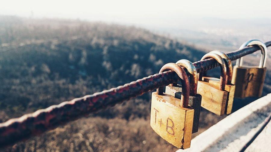Close-up of padlocks hanging on rusty railing