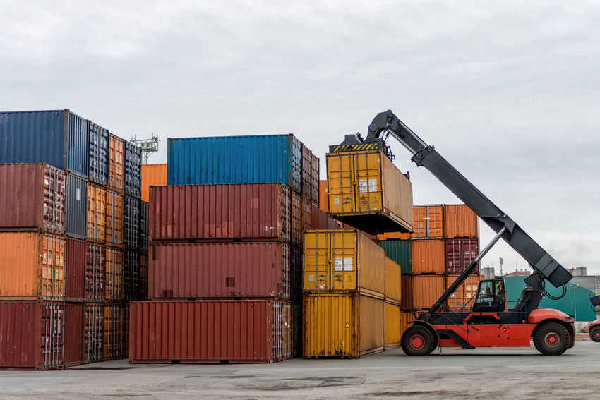 Mobile stacker handler in action at a container terminal. Cargo Container Commercial Dock Container Day Export Freight Transportation Harbor Import Industry Logistic No People Outdoors Shipping  Sky Stack Terminal Transfer Transportation