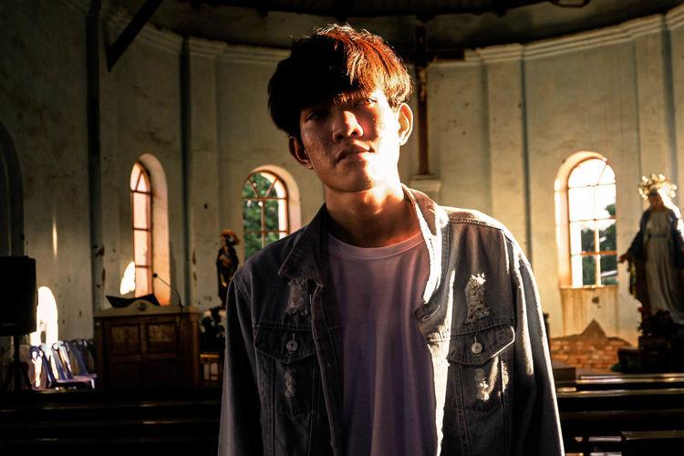 Young man looking away at illuminated church