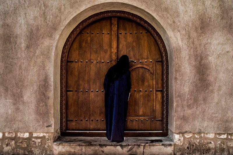Rear View Of Veiled Woman Looking Entering Through Wooden Door
