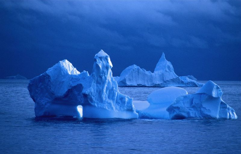 Ice Bergs On Sea Against Cloudy Sky At Night