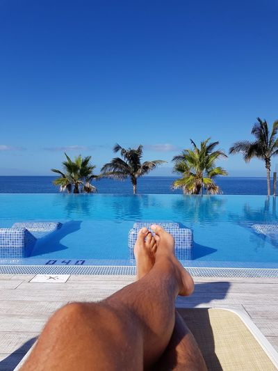 Low section of man relaxing on deck chair by infinity pool against blue sky