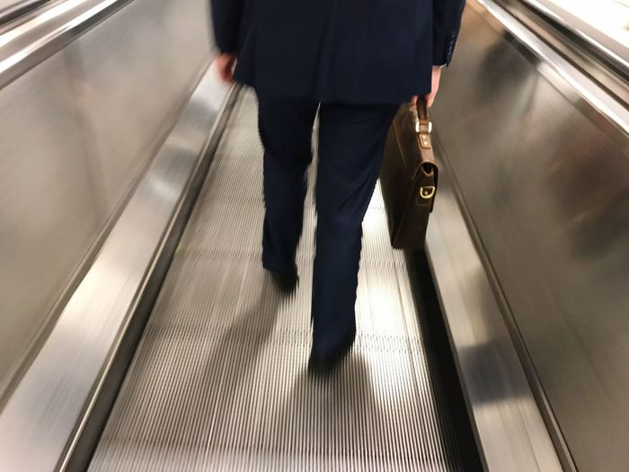 Blurred motion of people walking on escalator