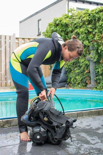 Woman Preparing Aqualung At Poolside