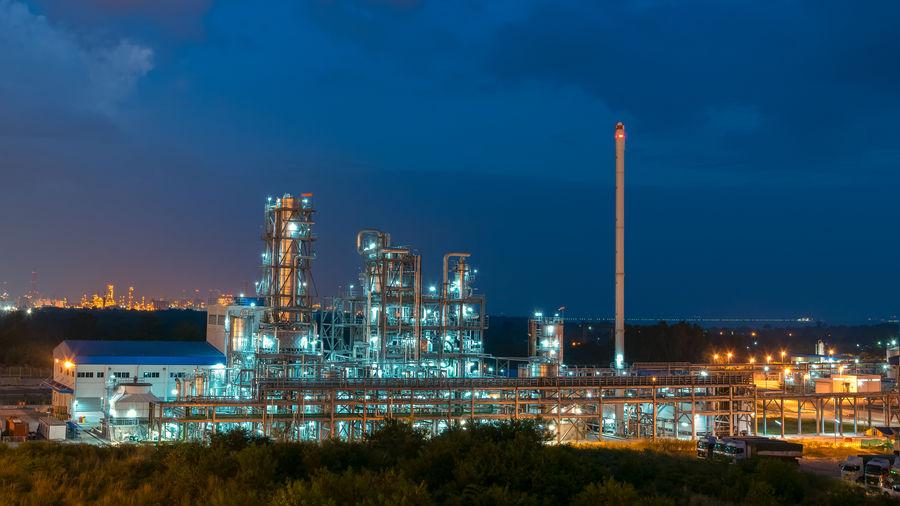 Illuminated factory against blue sky at night