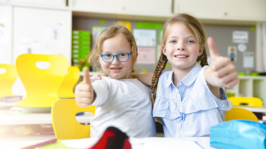 Portrait of cute friends gesturing while studying in classroom