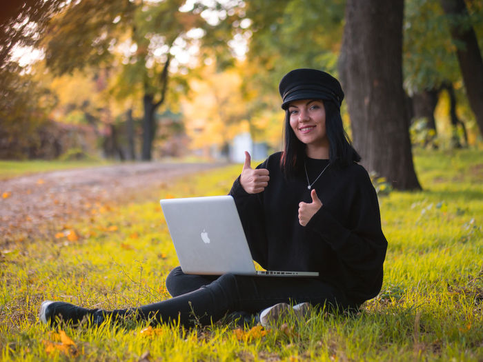 Portrait Of Young Woman Gesturing Thumbs Up While Using Laptop At Public Park During Autumn