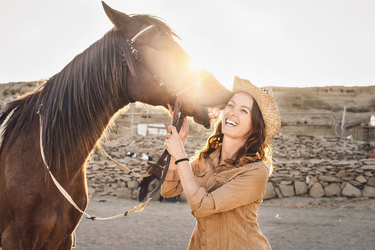 Smiling woman standing by horse