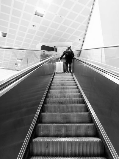Low angle view of man with luggage standing on escalator