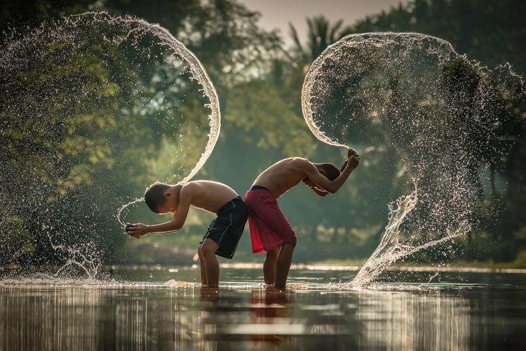 Shirtless boys splashing water in lake