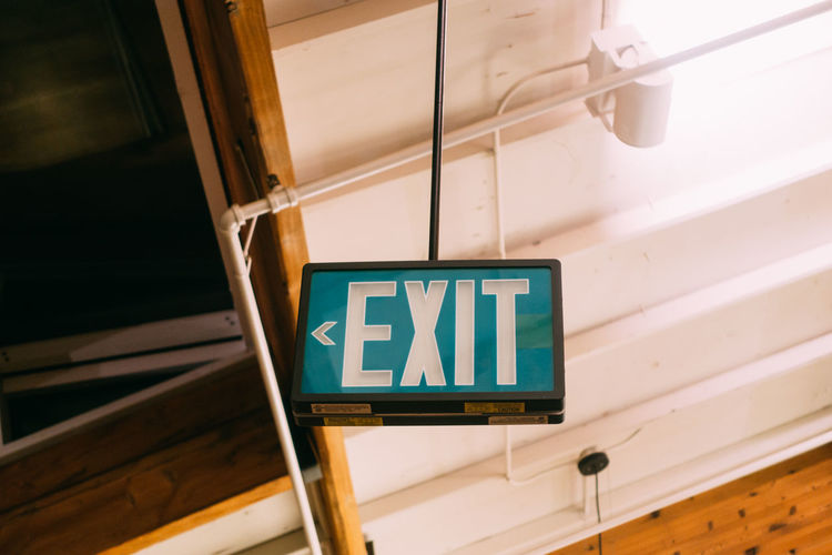 Low angle view of exit sign hanging from ceiling
