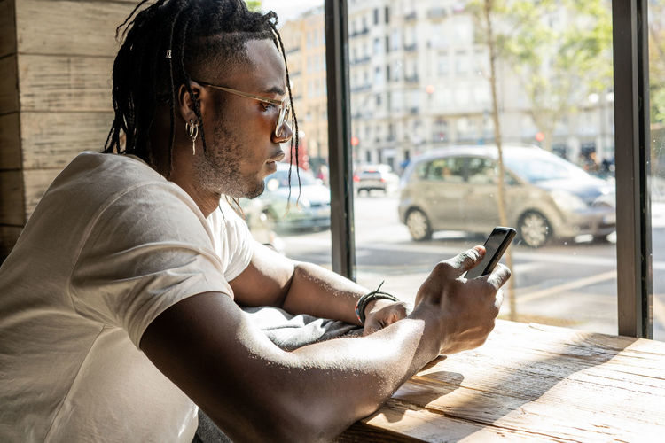 Side view of man using mobile phone while sitting in city