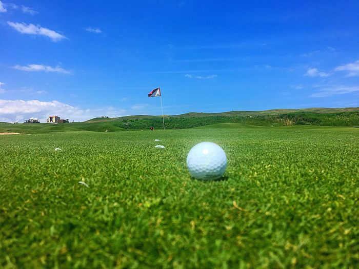 Golf Golf Course Green - Golf Course Grass Golf Ball Flag Cloud - Sky Sport Putting Green Green Color Sky Outdoors Day Tranquility Taking A Shot - Sport Leisure Activity Scenics Nature Blue Golf Club